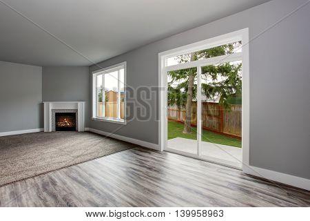 Grey Living Room Interior.  Windows And Glass Doors Overlooking The Back Yard.