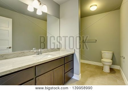 Light Bathroom Interior With Tile Floor And Vanity Cabinet With Large Mirror.
