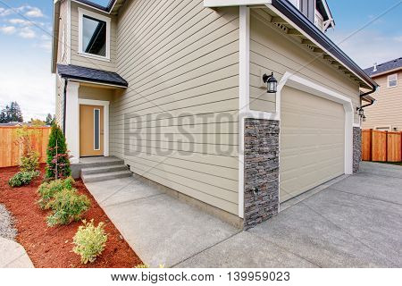 Beige House With Concrete Walkway To The Entrance Door.