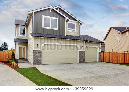 American House Exterior With Two Garage Spaces, Concrete Floor Driveway.