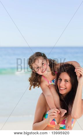 Mother Playing With Her Daughter On The Beach