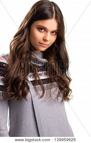 Calm woman in gray sweatshirt. Lady with long brown hair. Young model with cute face. Keeping the eye contact.