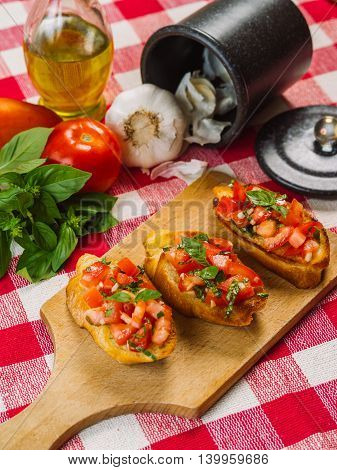 Photo of Italian bruschetta on a wooden board with the ingredients behind. Focus across the middle.