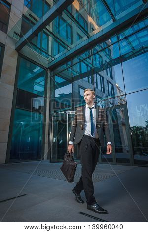 Young handsome successful stylish businessman walking near modern office building. Concept: victory.
