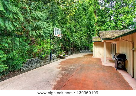 House Exterior. Concrete Back Yard With Patio Area And Basketball Hoop.