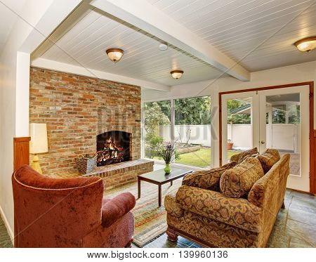 View Of The Living Room Area With Brick Wall And Fireplace, White Wooden Ceiling.