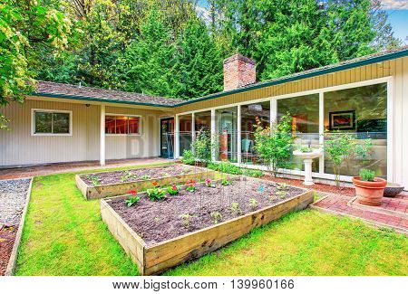 Beautiful Front Yard Landscape With Vegetable Garden And Red Tile Walkway.