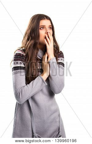 Girl covers face with hand. Scared woman on white background. Fear of the problem. Feeling the responsibility.