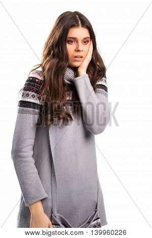 Woman holds hand on face. Girl in gray patterned sweater. Nervous and terrified state. See no chances.