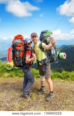 Couple of hikers taking selfie with mountains view on the background. Couple tourists woman and man make selfie in mountains. Active tourists
