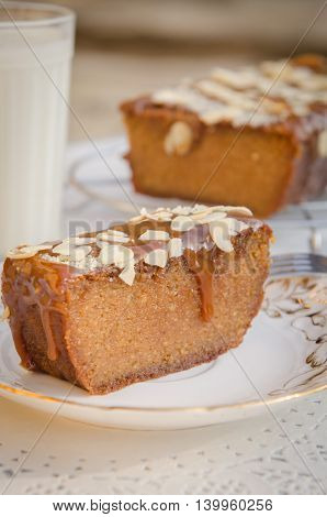 a piece of caramel cake with cinnamon and almonds on a plate