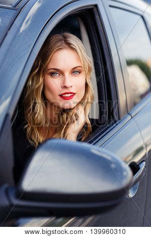 Cute girl with blond hair and natural make-up sitting in the blue car and looking out the window
