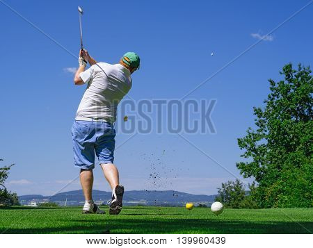 Photo of a male golfer hitting the ball down the fairway on a golf course. Slight motion blur visible.