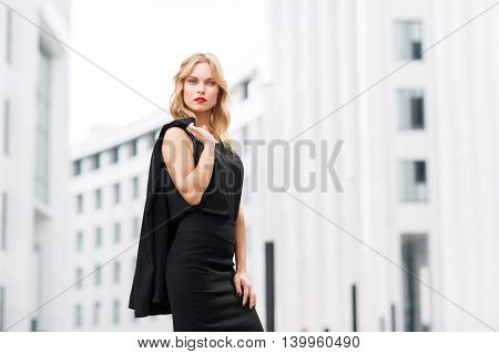 Serious successful business woman in black suit against white modern business centers