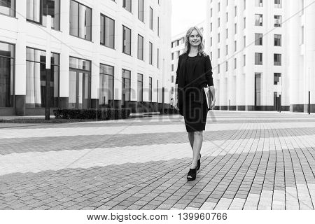 Black-and-white portrait of stylish successful business woman among modern office buildings