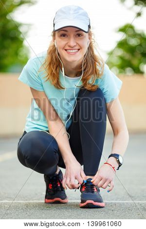 Beautiful Young Woman Tying Her Laces Before A Run.