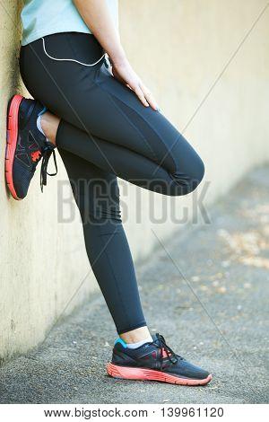 Female Runner Holding Her Hand On Injured Leg.