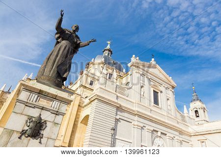 Pope John Paul II statue in front of Cathedral Almudena in Madrid, Spain.