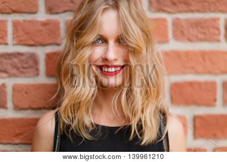 Closeup portrait of blonde woman with curly hair on brick background. Shoot on fast aperture