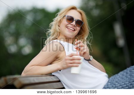 Laughing blond girl in sunglasses sitting on park bench with cup of drink to go. Image with tilt-shift effect