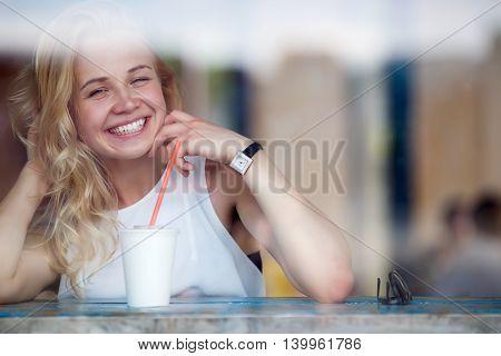 Portrait of smiling blonde woman enjoying her milkshake sitting in coffee. Image taken through a window