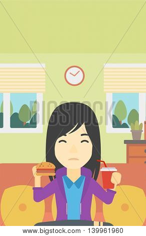 An asian young woman sitting on a sofa while eating hamburger and drinking soda on the background of living room. Vector flat design illustration. Vertical layout.