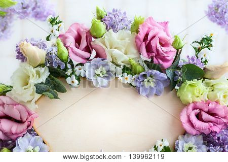 Festive frame with fresh flowers and wooden greeting card