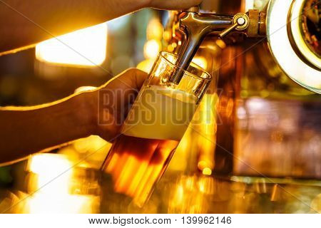 Male hand poured beer indoors