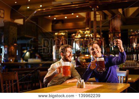 Young men make selfie in a pub