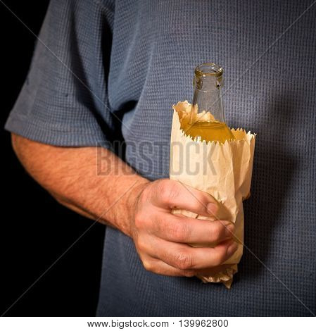 drinker holds a bottle in the paper bag shallow depth of field