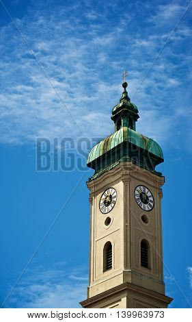 Clock Tower Heilig Geist Kirche against Blue Cloudy Sky Outdoors. Munich Germany