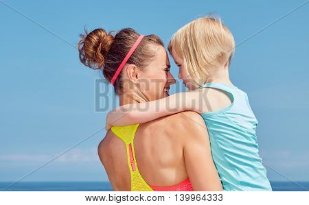 Seen From Behind Fitness Mother And Child Hugging On Embankment