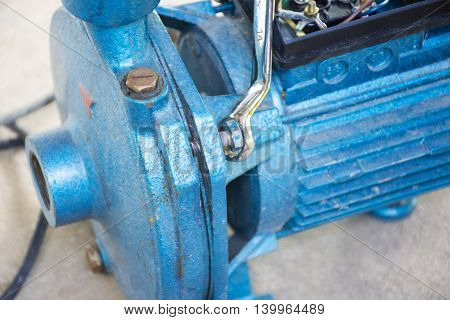 Electric motor  and man working equipment repair on cement floor background.Background motor or equipment.Close up.
