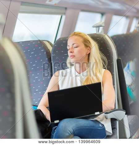 Businesswoman naping sitted while traveling by train and working on laptop. Tiresome business travel.