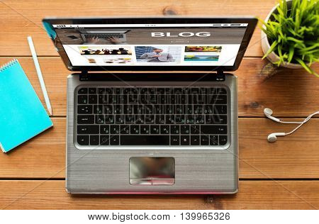 mass media, internet, business and technology concept - close up of laptop computer with blog web page on screen on wooden table