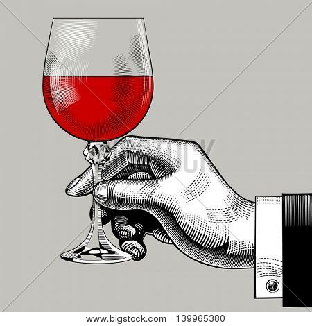 Hand holding a glass with red wine. Vintage engraving stylized drawing. Contains the Clipping Path