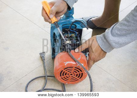 Electric motor  and man working equipment repair on cement floor background.Background motor or equipment.Zoom in 03
