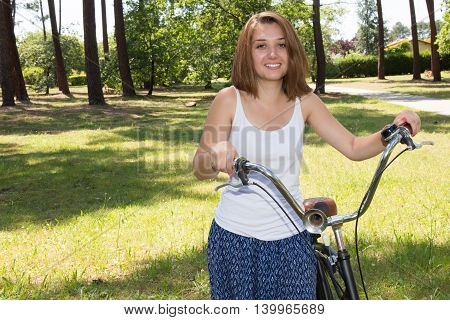 Portrait of Attractive Young Woman in blue shirt with cool beach cruiser bike close up