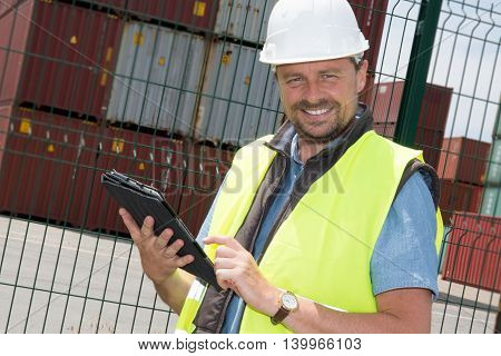 Man Worker With Tablet And Standing Before Stack Of Containers