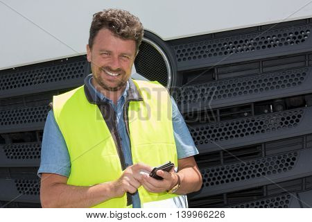 Road Construction Worker Using Mobile Phone Standing In Beside Truck