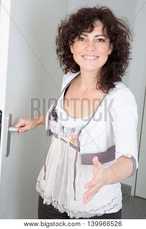 Woman opening her house door to welcome the people