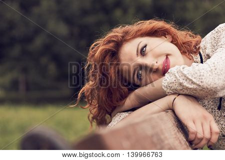 Girl with red curly hair siting on a bench in the park with her head leaning on her hands looking into distance. Plenty of copy space