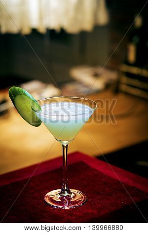 cucumber mint modern trendy martini cocktail in bar at night