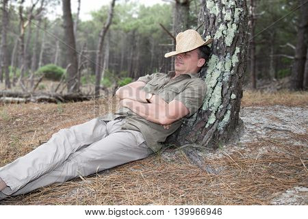Cheerful man relaxing leaning on Tree with hat