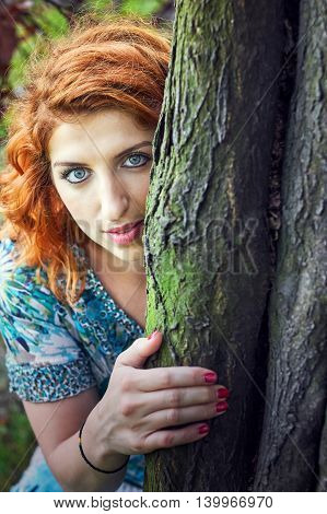 Girl with red hair and blue eyes peeking behind tree. Copy space