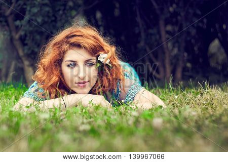 Girl with red hair and blue eyes lying in the grass on her stomach looking to the right with dark foliage in background. Copy space