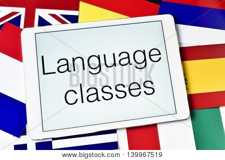 the text language classes in the screen of a tablet computer surrounded by flags of different countries