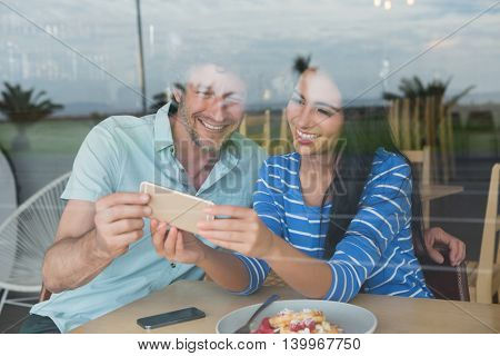 Happy couple using mobile phone in cafeteria