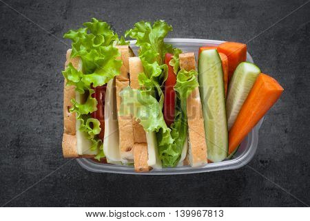 Lunch box with sandwich on black background. Healthy eating. Flat lay.