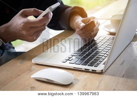 Online payment Man's hands holding a credit card and using smart phone for online shopping with vintage filter effect